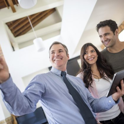 Real estate agent showing house to a couple and holding a digital tablet