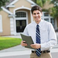 Mid adult man (30s) standing in front of house.